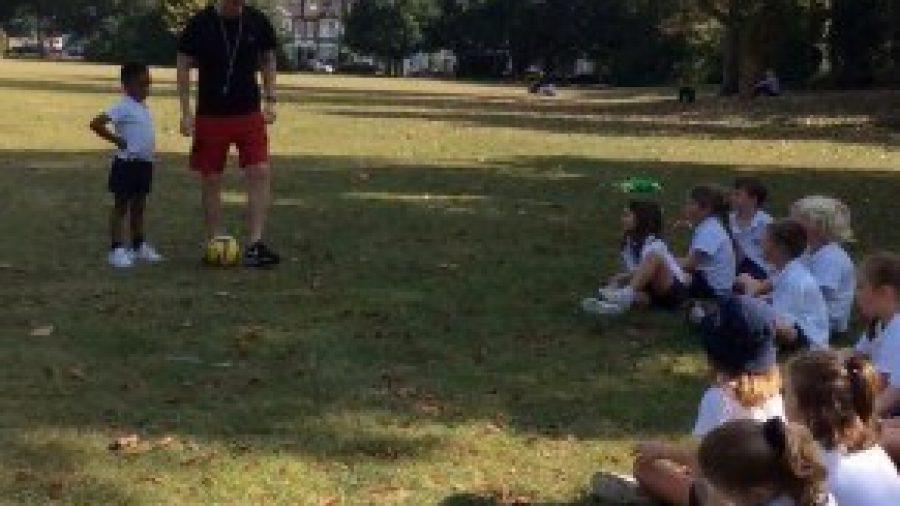 Years 1 & 2 practise dribbling skills in Football